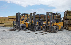 Sunstate timbers yard with stack of timber and yellow forklifts parked outside