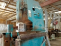 An inside view of a warehouse and timber cutting machine