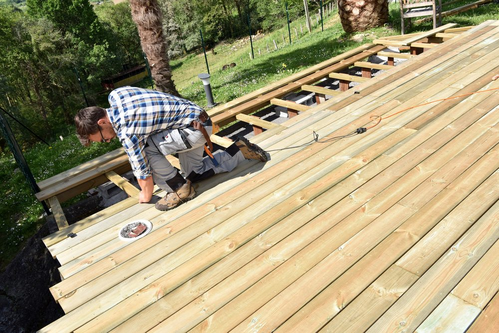 A man building a wooden deck