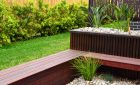 Hardwood timber structures with plants in white stones near green lawn