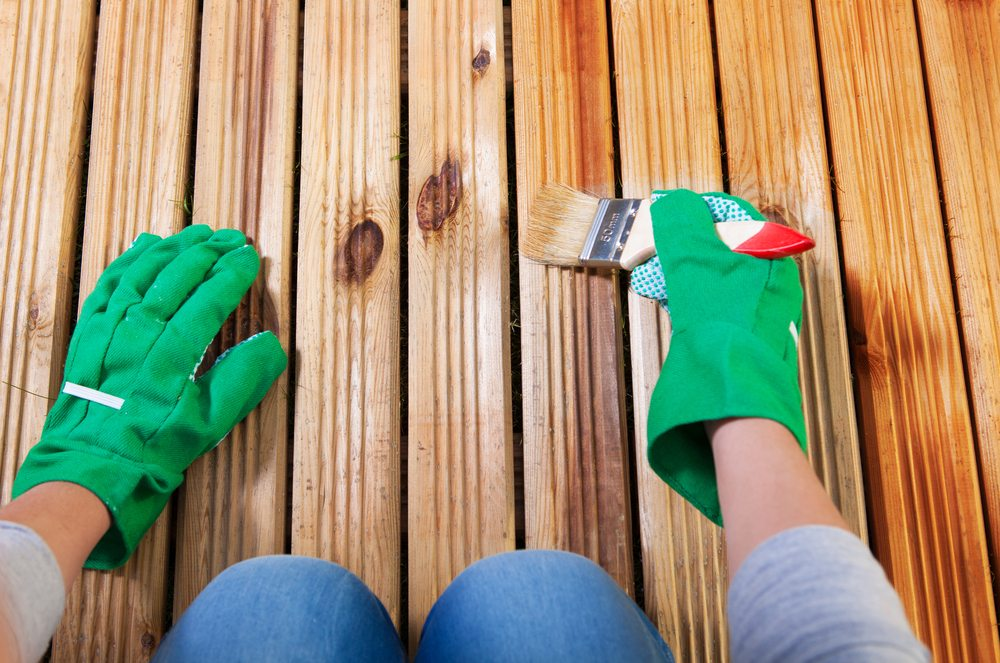 Person wearing gloves and staining the deck