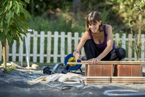 Woman measuring wood for carpentry in her back yard