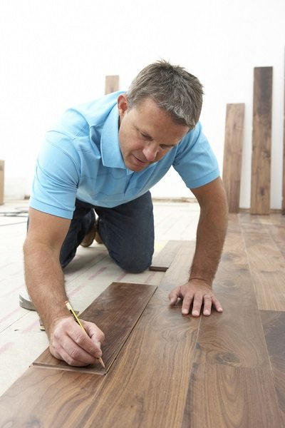 A builder laying wooden flooring