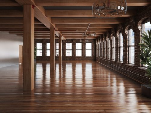 Empty room interior of a residence or office space with rustic timbers and highly polished matching timber floors.