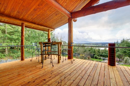 Large deck in new timber porch with stained timbers with small table and chair overlooking forest view