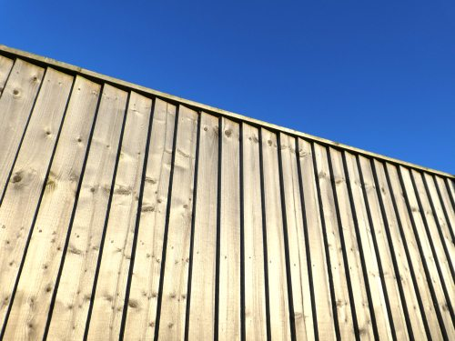 Treated pine wooded fencing panels against blue sky