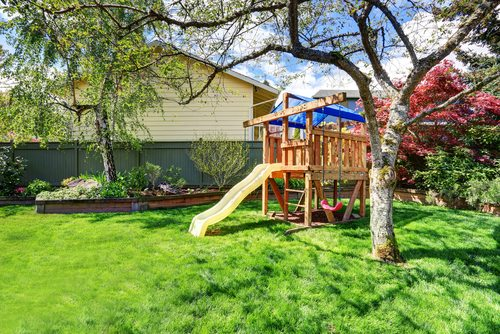 View of kids' timber playhouse in green backyard garden with birch trees and flower bed.