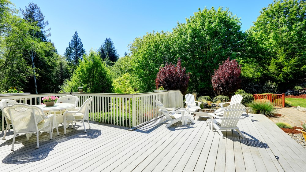 Backyard deck with white chairs