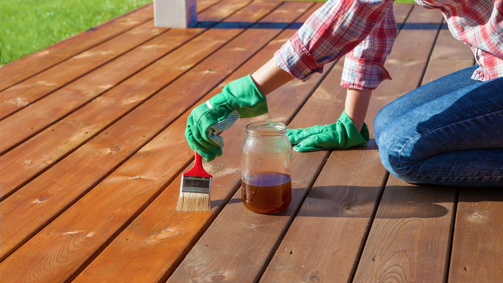 Woman applying protective varnish or wood oil on a patio wooden floor