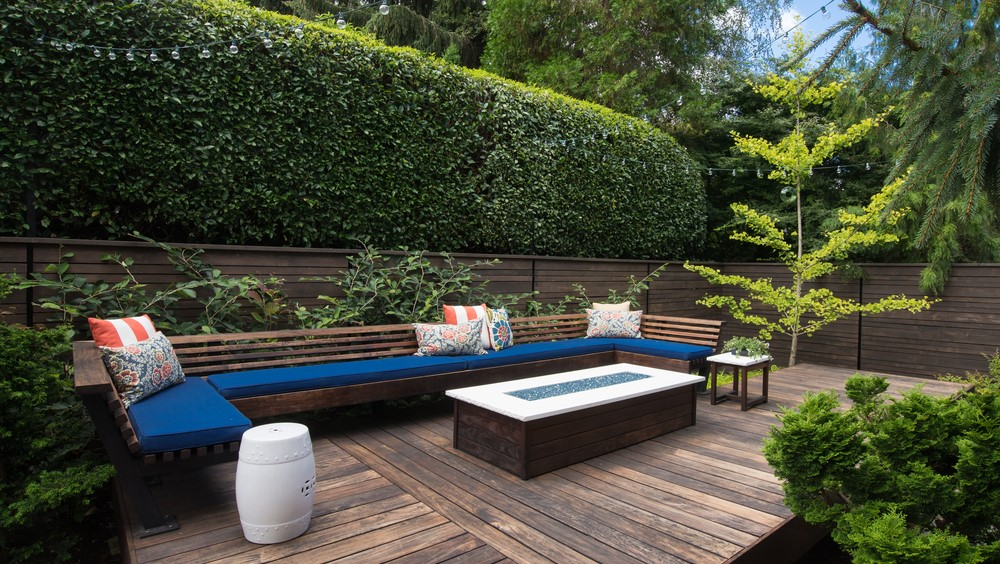 Contemporary outdoor conversation bench with pillows on a wooden deck
